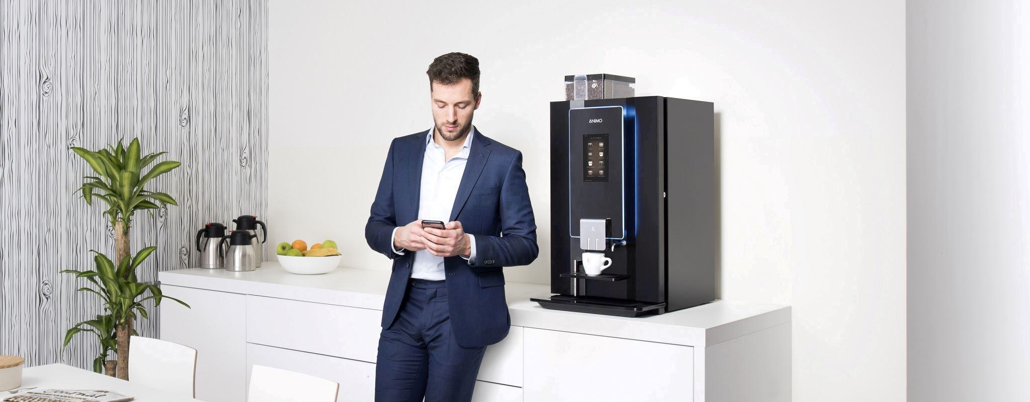 Mitarbeiter steht in der Küche vor Kaffeemaschine OptiBean Touch